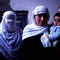. HOTAN, 3 OCOTBER 2001: 2 Uighur women hold a baby in the mosque in Hotan .Uighur muslims in southern Xinjiang province lead very basic lifestyles and have an average monthly income of about 50 US$.. (photo by: katharina hesse/Grazia Neri).