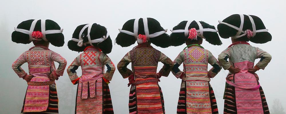 Long Horn Miao little girls in traditional costumes dancing to celebrate Flower Dance Festival, Suoga, Guizhou, China