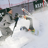 Photographer Rick Wilking scrambles to get out of the way of Germany's ski racer Maria Riesch as she crashes during the first run of the Women's World Cup  Slalom  in Aspen, Colo., on Sunday, Nov. 26, 2006.   (AP Photo/ Nathan Bilow)