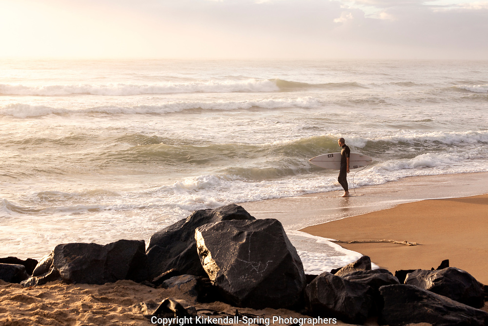 NC00816-00...NORTH CAROLPNA - Surfer at Cape Hatteras Lighthouse Beach, Cape Hatteras National Seashore. (No MR)