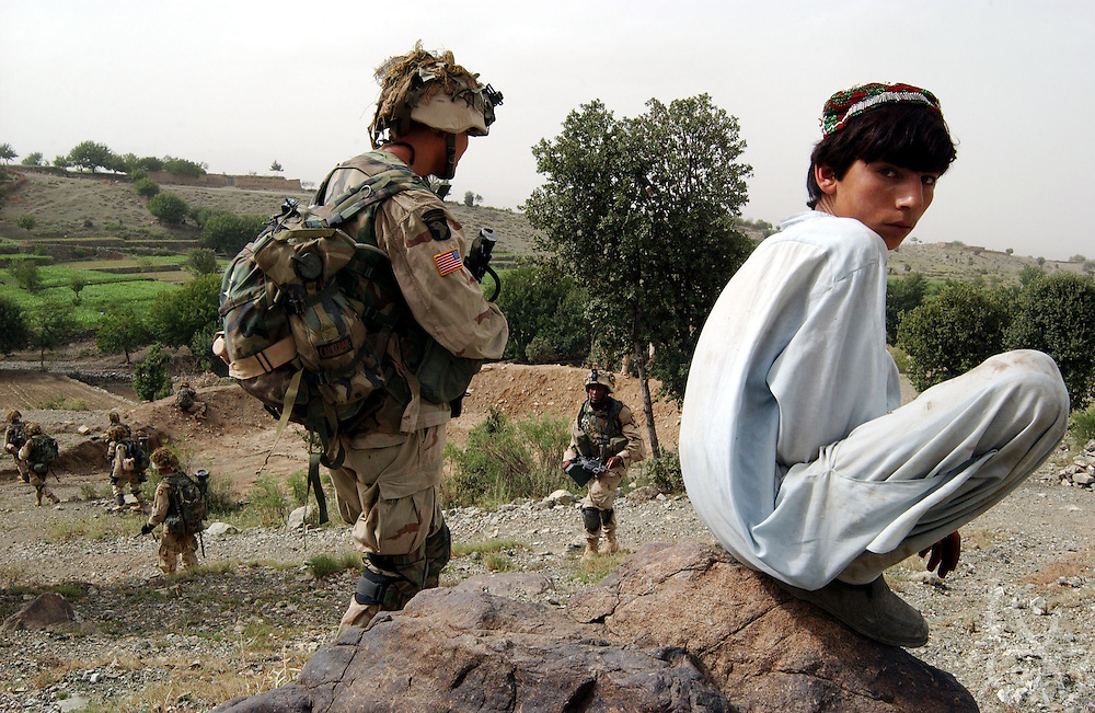 "An Afghan boy watches as US Army 101st Airborne 3-187 ""Bravo"" company move in during a 23 July, 2002 sensitive site exploitation (SSE) mission in the town of Narizah in Southeastern Afghanistan . The three day mission, intended to deny sanctuary to Al Qaida and Taliban fighters in villages along the Pakistan-Afghanistan border resulted in the recovery of several weapons caches and one Afghan detained for questioning."