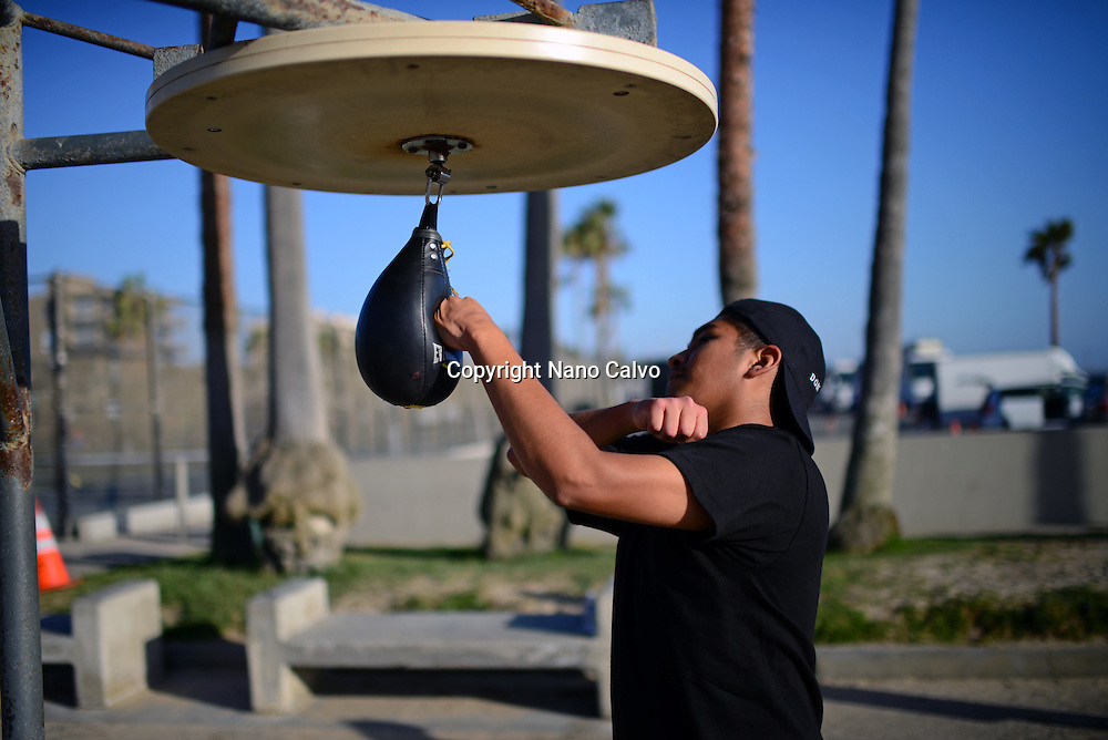 Young man practicing with the boxing speed bag on Venice Beach, California.