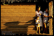 Rubber tapper's wife, kids @ doorway of their rustic Amazon home, sunrise;Acre state;Sta Queteiria Brazil