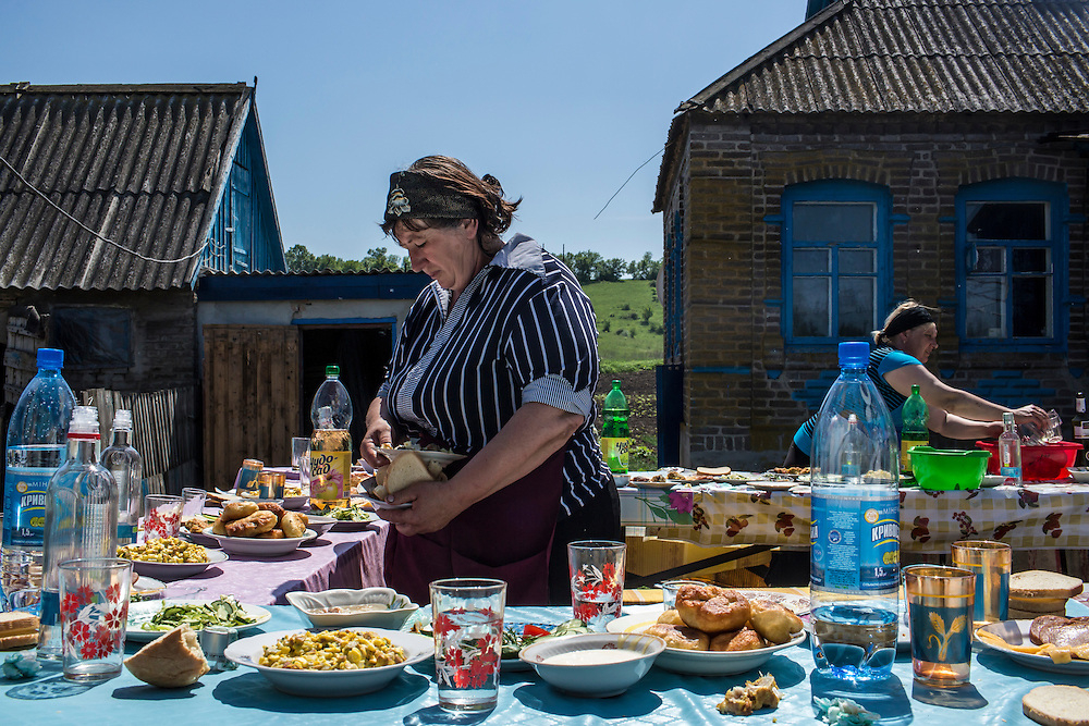 STAROVARVAROVKA, UKRAINE - MAY 16:  Women clean up following a communal meal after the funeral of Elena Ott, 42, on May 16, 2014 in Starovarvarovka, Ukraine. Ott was killed two days prior when the car she was riding in was fired on by forces her family believes to be the Ukrainian military. (Photo by Brendan Hoffman/Getty Images) *** Local Caption ***