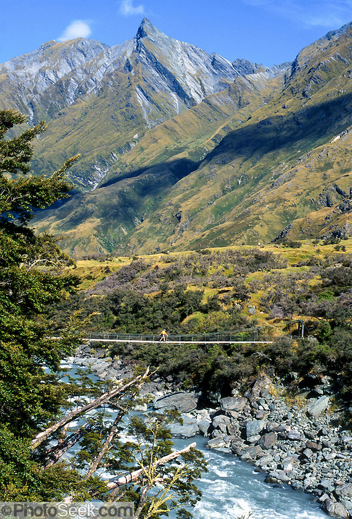 South Island, NEW ZEALAND: A day hiker crosses Matukituki River swing bridge beneath rocky peaks of the Southern Alps. Published in Sierra Magazine, Sierra Club Outings November/December 2002. In 1990, UNESCO honored Te Wahipounamu – South West New Zealand as a World Heritage Area.