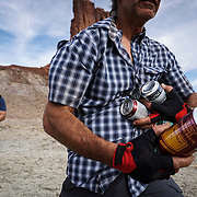 SHOT 10/14/16 3:48:10 PM - Beers during a pit stop along the White Rim Trail. The White Rim is a mountain biking trip in Canyonlands National Park just outside of Moab, Utah. The White Rim Road is a 71.2-mile-long unpaved four-wheel drive road that traverses the top of the White Rim Sandstone formation below the Island in the Sky mesa of Canyonlands National Park in southern Utah in the United States. The road was constructed in the 1950s by the Atomic Energy Commission to provide access for individual prospectors intent on mining uranium deposits for use in nuclear weapons production during the Cold War. Four-wheel drive vehicles and mountain bikes are the most common modes of transport though horseback riding and hiking are also permitted.<br /> (Photo by Marc Piscotty / &copy; 2016)