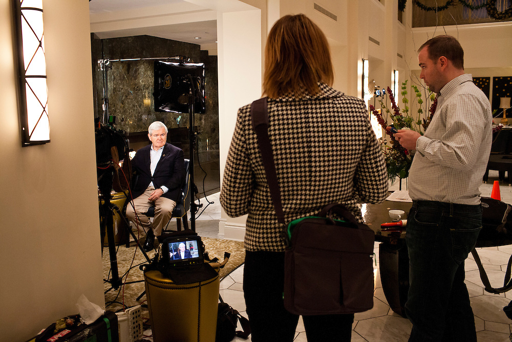 Republican presidential candidate Newt Gingrich talks with aides before a television interview at the Hotel Blackhawk on Tuesday, January 3, 2012 in Davenport, IA.