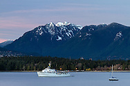 The fishing charter yacht M.V. Edgewater Fortune anchored in English Bay.  In the background is Stanley Park, Crown, Goat and Grouse Mountains with some fresh, spring snowfall, and some sunset light on the high clouds above.  Photographed from Kitsilano Beach Park in Vancouver, British Columbia, Canada.