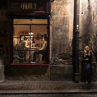 A couple sits in a restaurant while a girl smokes outside. Krakow, Poland