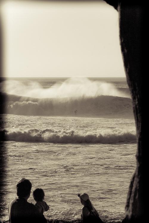 A family watches a surfer at Banzai Pipeline from Ehukai Beach Park, Oahu, Hawaii, USA.
