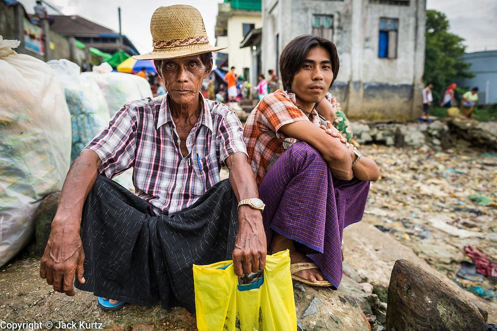 09 JUNE 2014 - YANGON, MYANMAR: Men wait to board cross river ferries on the Yangon side of the Yangon River near San Pya (also spelled Sanpya) fish market. San Pya Fish Market in Yangon is one of the largest wholesale fish markets in Yangon. The market is busiest in early in the morning, from before dawn until about 10AM.    PHOTO BY JACK KURTZ