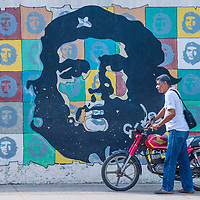 HAVANA, CUBA - JULY 18 : A man with a motorcycle walking past a mural of Che Guevara in old Havana street on July 18 2016. The historic center of Havana is UNESCO World Heritage Site since 1982.