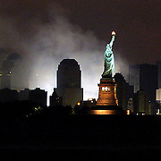 The Statue of Liberty remains a symbol of strength and freedom even as the remains of the World Trade Towers continue to smolder. Giant work lights illuminate ground zero as rescue efforts continue throughout the night a week following the attacks.