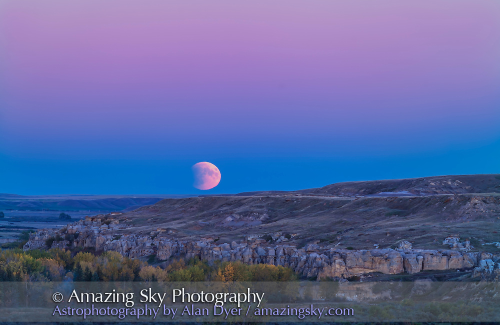 The Full Moon rises in partial eclipse over the sandstone formations of Writing-on-Stone Provincial Park in southern Alberta, on the evening of September 27, 2015. This was the night of a total lunar eclipse, which was in progress in its initial partial phase as the Moon rose this night. The blue band on the horizon containing the Moon is the shadow of Earth on our atmosphere, while the dark bite taken out of the lunar disk is the shadow of Earth on the Moon. The pink band above is the Belt of Venus. <br /> <br /> This is a two-image panorama stitched to extend the scene vertically to take in more sky and ground than one frame could accommodate. Both shot with the 200mm lens and 1.4x extender, on the Canon 5DMkII.