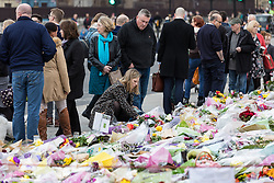 © Licensed to London News Pictures. 29/03/2017. London, UK. A woman lays flowers in Parliament Square in memory of the victims of the Westminster terrorist attack. Photo credit: Rob Pinney/LNP