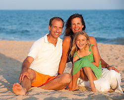 family of three enjoying time together at the beach
