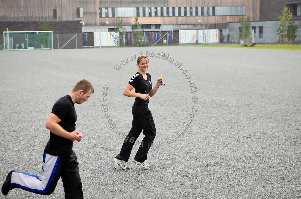 A woman trainer (right) is running alongside an inmate in the yard of the luxurious Halden Fengsel, (prison) during the time prisoners regularly spend carrying out physical exercise and learning about the human body in Halden, near Oslo, Norway.