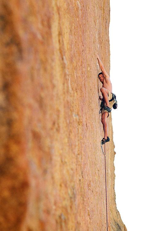 A young man rock climbing at Smith Rock State Park, Oregon.