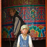 """A woman turns a Mani Thungkyur (a large prayer wheel, which may contain religious books) while a girl looks out the door, at Pangboche Gompa (temple), Nepal. Buddhism became firmly established in Nepal's Khumbu District (home of the Sherpa people) about 350 years ago by the power and influence of Lama Sangwa Dorje. He established the oldest monastery in Khumbu at Pangboche (plus many other small hermitages). Sagarmatha National Park was created in 1976 and honored as a UNESCO World Heritage Site in 1979. Published in """"Light Travel: Photography on the Go"""" book by Tom Dempsey 2009, 2010."""