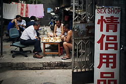 Men play Chinese chess beside a sex shop in an old back alley of Beijing, China, Asia