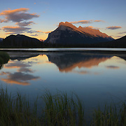 Mount Rundle is reflected in the still waters of one of the Vermillion Lakes in Banff National Park, Alberta, Canada.