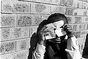 IPLM0028 , South Africa, Soweto, June 2001. A primary school girl plays around with a paper mask after school.