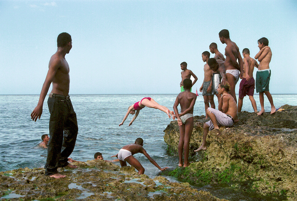 A group of Cuban guys watch as a young American woman dives into the water along the Malecón in Havana, Cuba.