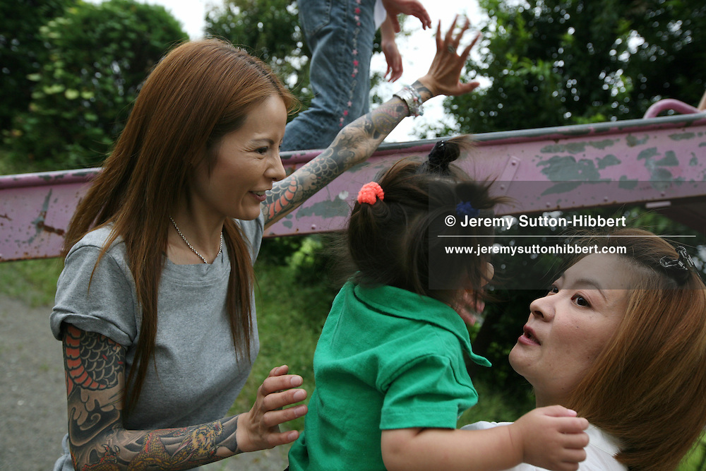 Shoko Tendo reveals her Yakuza style tattoos on her arms (something she rarely does) as she plays with her two year old daughter Komachi (in green), and her sister Maki (in white) and Maki's daughter Shiho (in denims on slide), in Honjo near Tokyo, Japan, Saturday, Sept. 1st, 2007. Shoko Tendo, daughter of Yakuza boss Hiroyasu Tendo (now deceased) has written an autobiographical book - 'Yakuza Moon',  describing her life growing up with a Yakuza criminal boss for a father, of her addiction to drugs, and the failed, and often violent sexual relationships she had with men. Shoko Tendo has a body covered in Yakuza style tattoos, including a large depiction of the Muromachi-period courtesan Jigoku Dayu (with a dagger clenched in her teeth), on her back. Shoko Tendo now lives in Tokyo with her 2 year old daughter Komachi.