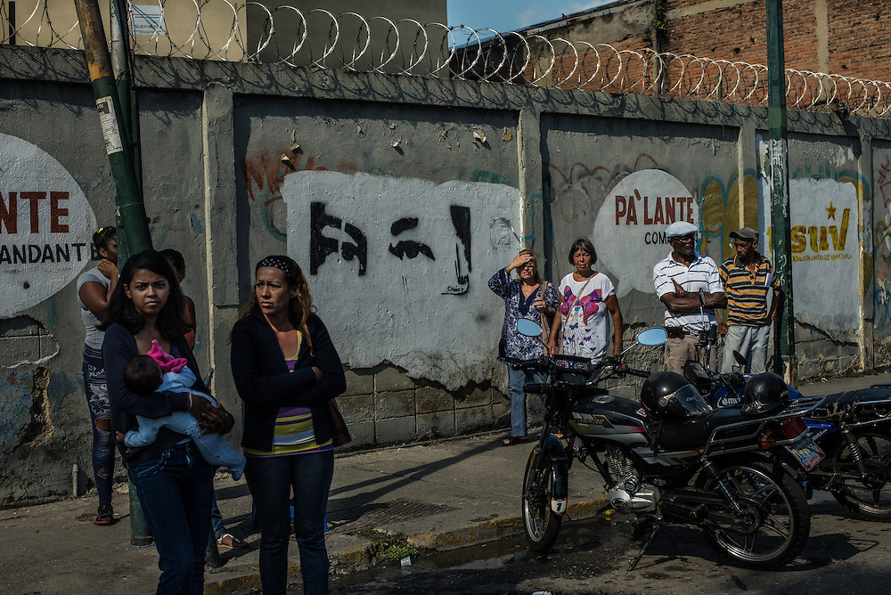 CARACAS, VENEZUELA - NOVEMBER 14, 2016: Bystanders watch as police and investigators work a triple homicide crime scene in El Cementerio neighborhood in Caracas.  A severe economic crisis in Venezuela, caused by the drop in oil prices and years of economic mismanagement under a Socialist government, has lead to an alarming rise in crime and insecurity in the country.  Hyperinflation has left both the working class and professional class of workers with salaries that cannot purchase enough food to feed their families. Many people are turning to crime to make ends meet.  PHOTO: Meridith Kohut for The New York Times
