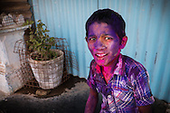 Indian boy painted with colours during Holi festival in streets of Hampi, Karnataka, India, on  March 5, 2015. Holi, also known as the Festival of Colors, heralds the beginning of spring and is celebrated all over India.<br /> Photo by Oren Nahshon