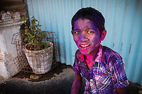 Indian boy painted with colours during Holi festival in streets of Hampi, Karnataka, India, on  March 5, 2015. Holi, also known as the Festival of Colors, heralds the beginning of spring and is celebrated all over India.<br />
