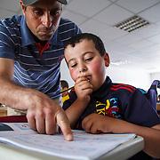 Khalid receives instruction in class. Zaatari camp for Syrian refugees, Jordan, March 2014.
