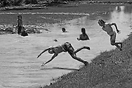 Cambodian children play in an irrigation canal during the heat of the day in Pursat Province.