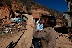 A picture made available on 06 November 2012 of Chinese corn farmer Yang Zhichong holding his one-year-old nephew outside their cave home or 'yaodong' in the rural outskirts of Yan'an city, Shaanxi Province China, 05 November 2012. Yang's family of five struggle to survive on their yearly income of 10,000 RMB (1,248 euros) from growing and selling corn. Their cave home is in danger of collapsing but there was no money to carry out repair work. The 'yadong' or cave dwellings are typical in the plateaus of northern China in Shaanxi Province where many of Yan'an's rural population still live in. They are mostly carved out from the yellow earth of the Loess hillsides and are about seven to eight metres deep with height and width of three metres. Former Communist leader Mao Zedong and his comrades are known to have hid in these cave homes during the civil war between the communists and nationalists in 1936 to 1948 as they battle the Kuomintang forces. Chao has lived in his cave home in the Loess mountains of Yan'an for more than 60 years, mostly in poverty and hardship as a farmer and was one of the few to have lived through the period of turmoil during the civil war. China's new leaders slated to take over during the 18th National Congress beginning on 08 November are likely to face mounting pressures to tackle the country's rising income inequalities between urban and rural areas that are often the source of simmering resentment and growing unrests on the grassroot level.