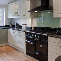 Kitchen interior with cream and green units, gas aga, cooker hood, belfast sink and wooden floor