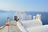 Two asian tourists taking pictures,Santorini, Kyclades,South Aegean, Greece,Europe