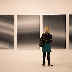 London, UK - 15 October 2014: a woman looks at artworks from the Almine Rech Gallery during the first day of Frieze Art Fair and Frieze Masters in Regent's Park.