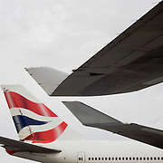 Wing tips and tail from British Airways 747 airliners are almost touching during their turnarounds while on  apron at Heathrow