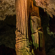 A mammoth column known as the Veiled Statue stretches from the floor to the ceiling of the King's Palace, a section of Carlsbad Caverns National Park in New Mexico. Columns, a type of speleothem, are formed when groundwater containing calcium bicarbonate solution seeps into the cave. Then that solution is exposed to the air in the cave, carbon dioxide gas is released and calcite is deposited.