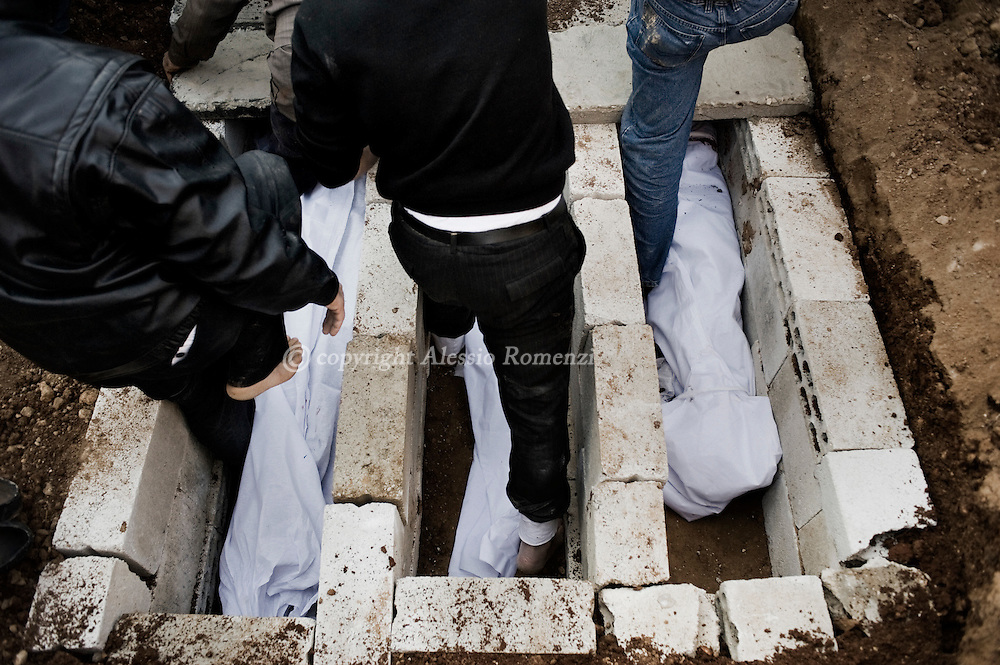 SYRIA - Homs province: Men set the graves of three shaheed (martir) killed by a mortar attack launched by Al Asad forces, among them two children, in Homs province on February 20, 2012. ALESSIO ROMENZI