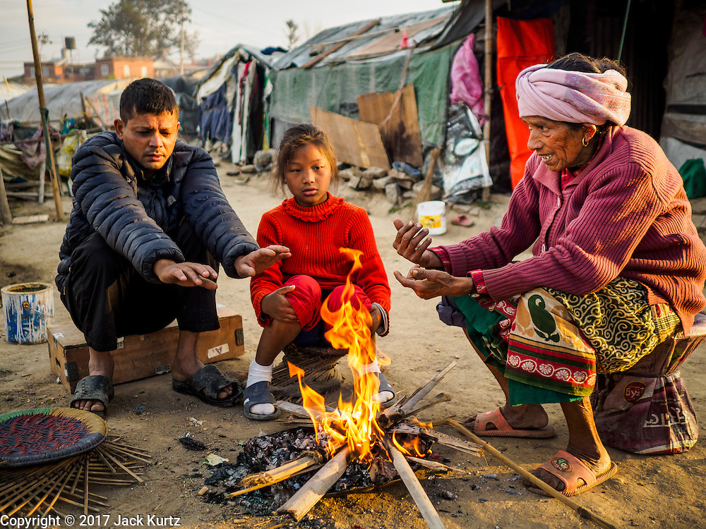 04 MARCH 2017 - KATHMANDU, NEPAL: A family from rural Nepal warms themselves by an open fire in an IDP camp in the center of Kathmandu. The nighttime low in Kathmandu is about 8C (45F) at this time of year, and the family lives in an unheated tent. The camp opened days after the April 2015 earthquake devastated Nepal, killing almost 9,000 people. At its peak, about 1,800 families lived in the camp. The camp is still open nearly two years after the earthquake, about 400 families currently live in the camp. Camp residents say the Kathmandu municipal government is trying to close the camp and is encouraging residents to find new housing. They said the government is cutting off services to the camp and last week stopped the free distribution of water, although water can be purchased for delivery. Most of the people in the camp came to Kathmandu from rural villages in the mountains in the weeks after the earthquake. Many of the residents of the camp, technically homeless, have found work in Kathmandu's bustling construction industry, rebuilding homes destroyed in the earthquake.       PHOTO BY JACK KURTZ