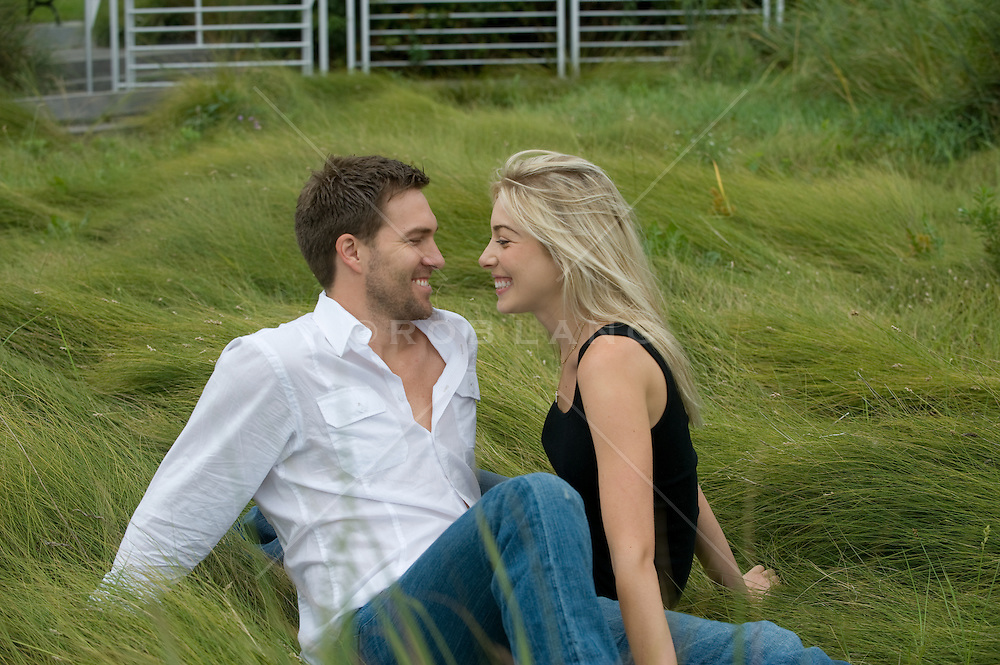 Young couple enjoying time together sitting in a field of green grass