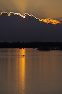 Light from the rising sun silhouettes a fishing boat as it heads toward deep water. Near Virginia Key in Biscayne Bay, Florida.<br /> WATERMARKS WILL NOT APPEAR ON PRINTS OR LICENSED IMAGES.