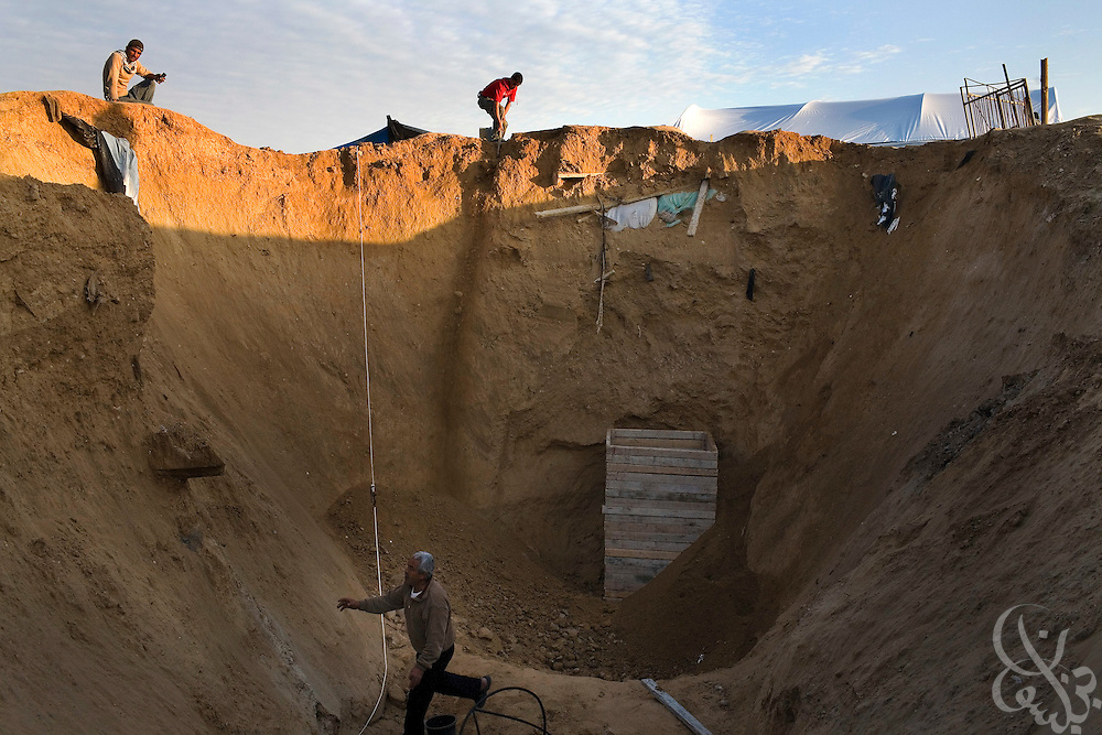 Palestinian workers dig above a bomb damaged smuggling tunnel entrance  on the Gaza-Egypt border in Rafah, Gaza January 21, 2009. Since the end of the 22 day Israeli military operation that included heavy airstrikes on the tunnel area, Palestinians have been busy reopening the undamaged tunnels, and rebuilding more heavily damaged or destroyed ones.  ..