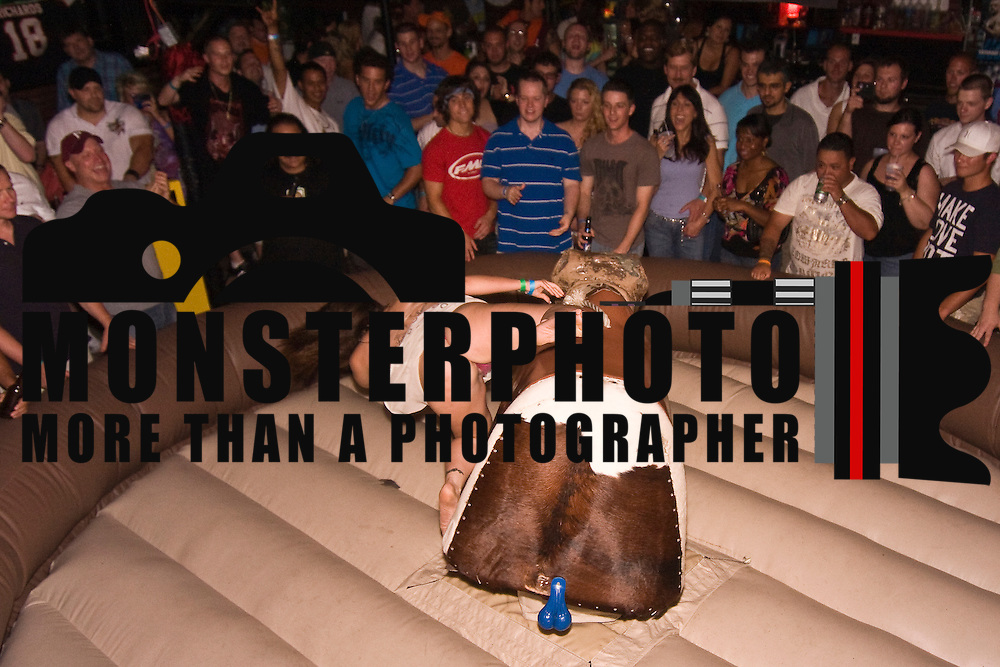 Legendary porn star Ron Jeremy Hosted a bikini contest in Hockessin Delaware. Scene in this photos is a candidate riding a mechanical bull in a dress. If you are going to ride a mechanical bull. Make sure you are wearing pants.