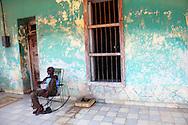 Man on rocking chair on a porch in San Antonio de Rio Blanco, Mayabeque, Cuba.