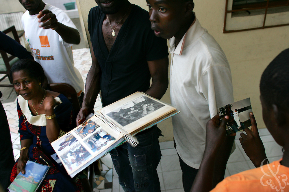 "The family of Ivory Coast national team member Didier ""Maestro"" Zokora look through a scrapbook of his news clippings and photos at their home in the Yopoungon neighborhood of Abidjan, Ivory Coast February 18, 2006. Zokora's mother Alphonsine (l), has founded a group called the ""mothers of the football playing elephants"" that meets monthly with the other mothers of national team members."