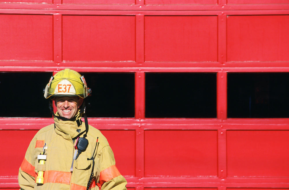 Portrait of smiling male firefighter with red garage door