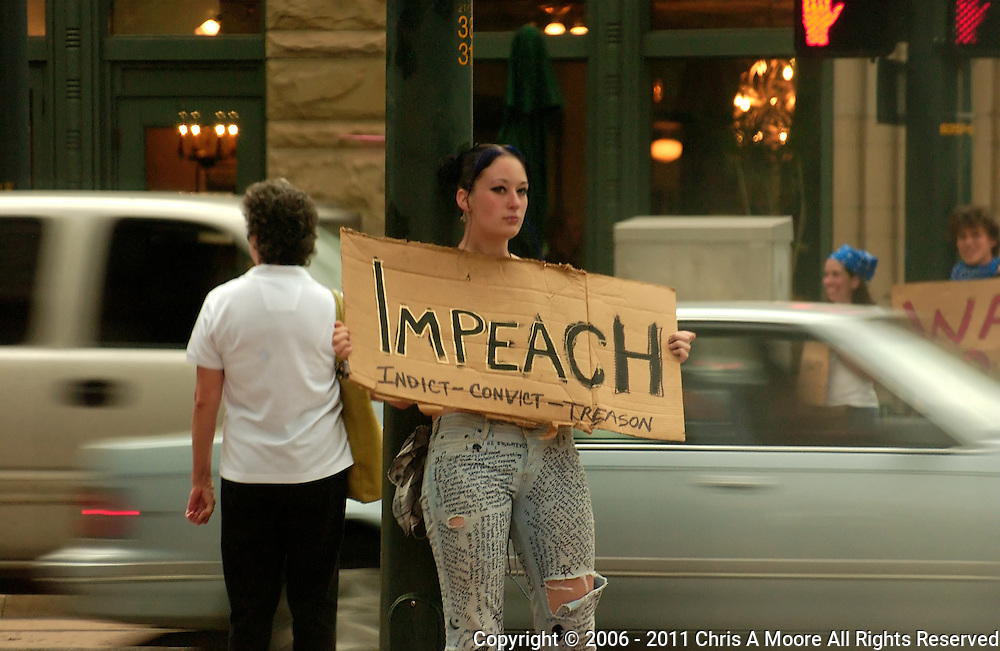 A young woman protests against the Wars in Iraq and Afghanistan by calling for Impeachment.  Her jeans are covered with her manifesto about war.  At 18th and Stout Streets, Denver, Colorado.
