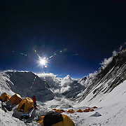 A climber stands outside his tent at sunset at 24,000 foot Camp 3 on Mount Everest's Southeast Ridge, Nepal.<br />